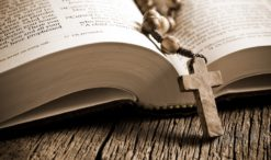 the wooden rosary on the open Bible